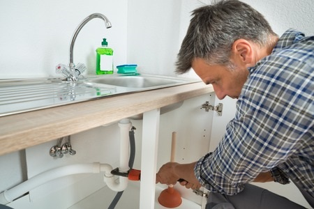 man in plaid shirt holding orange wrench on drain pipe under metal sink