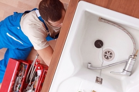 man sitting on kitchen floor next to tool box fixing unfinished faucet