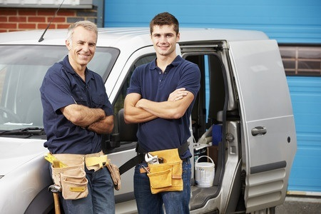 two plumbers in blue uniform with tool belts standing in front of open door on gray work van
